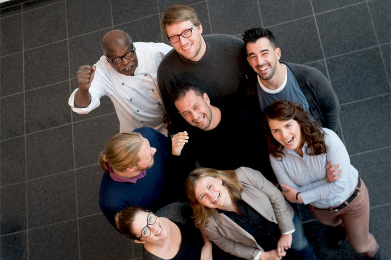 Eine Gruppe von lachenden Menschen von oben fotografiert.