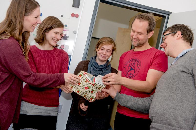 Drei Frauen und zwei Männer beugen sich über eine weihnachtliche Geschenktüte.
