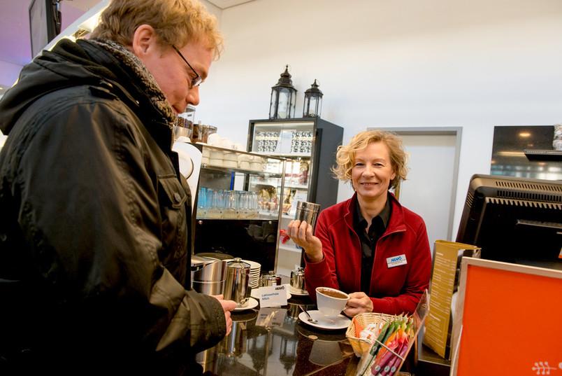 Eine Verkäuferin steht an einer Theke und streut Kakao auf einem Cappucino.