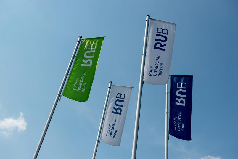 Vier Fahnen mit dem Schriftzug Ruhr-Universität Bochum RUB, zwei Fahnen sind weiß, je eine blau beziehungsweise grün