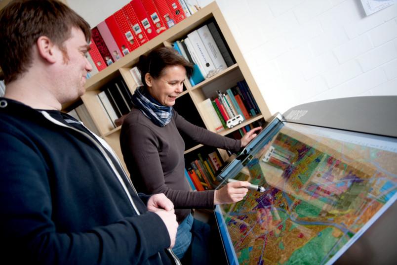 An einem speziellen Bildschirm besprechen Monika Steinrücke und ihr Kollege die unterschiedlich gefährdeten Bereiche Bochums.