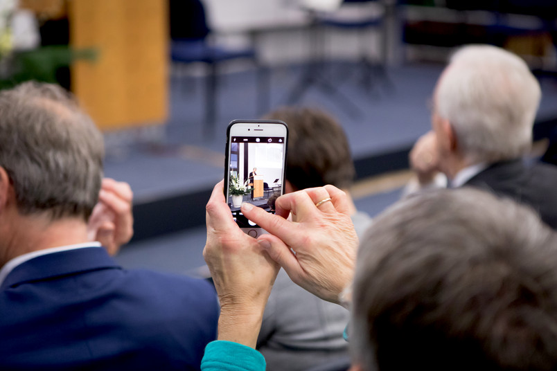 Zuschauer filmt Rede mit Smartphone