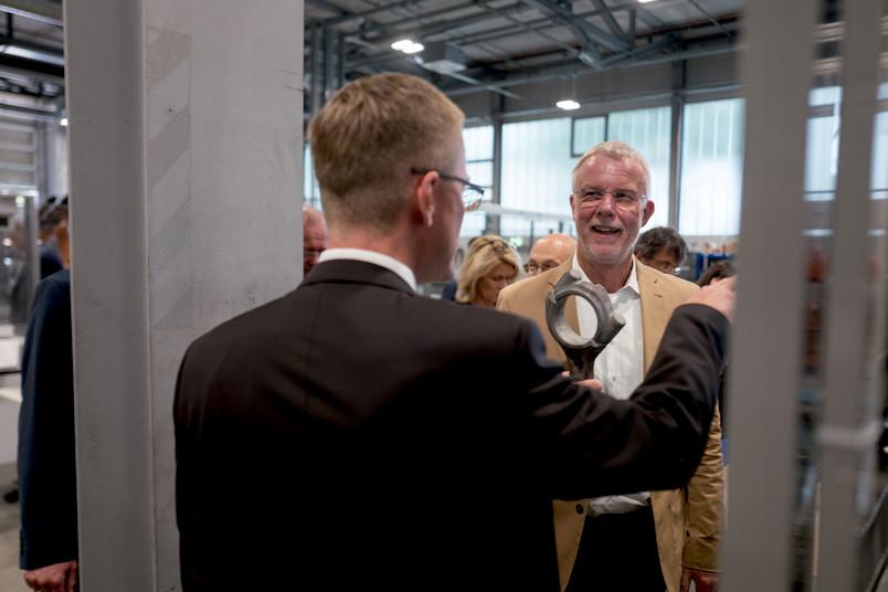 Zwei Männer in Anzügen in einer Fabrikhalle