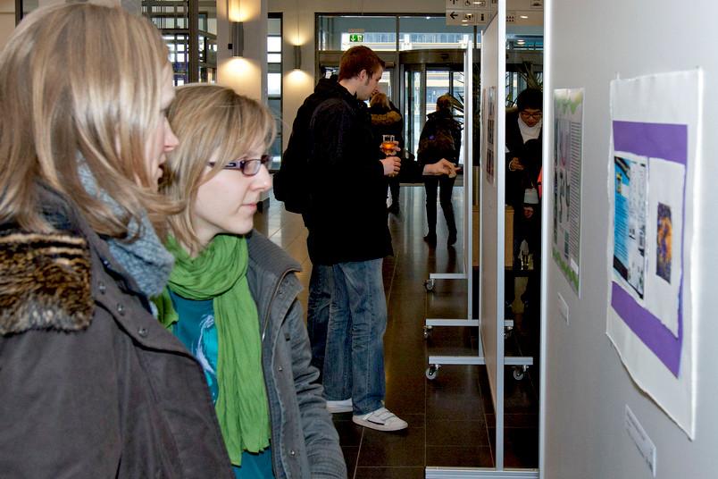 Die Ausstellung wurde gerade erst eröffnet, schon sehen sich die Gäste die Entwürfe an.