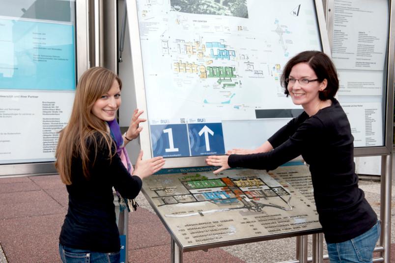 Zwei junge Frauen bringen einen Aufkleber an.