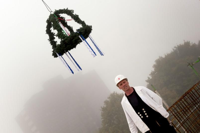 Richtkranz, Polier Manfred Geuecke von der Firma Rundholz und im Hintergrund im Nebel die alte Heimat der Sportler, das Unihochhaus West