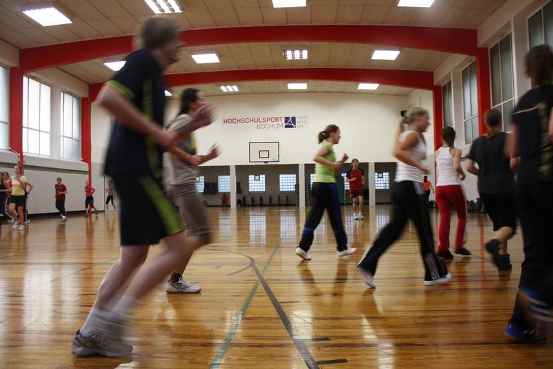 Menschen joggen in Sporthalle.