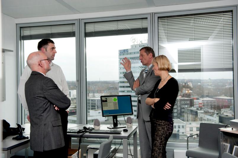 Prof. Dr. Jürgen Margraf (rechts), seine Frau Prof. Dr. Silvia Schneider und einer ihrer Mitarbeiter zeigen Rektor Prof. Elmar Weiler (links) die neuen Räume in der Stadtbadgalerie.