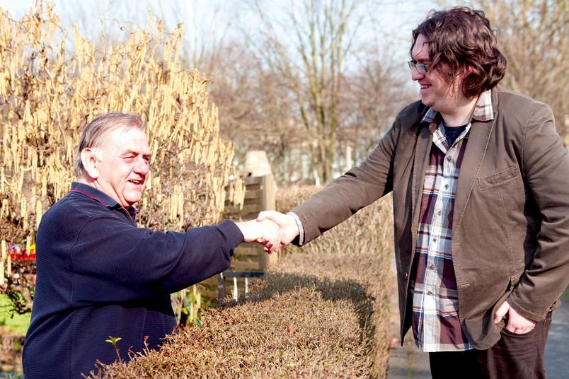 Zwei Männer reichen sich über eine Hecke hinweg die Hände.