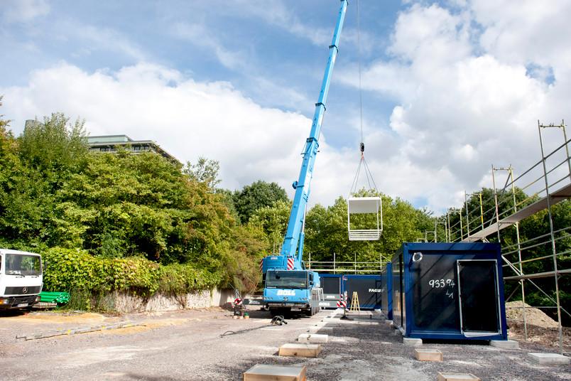 Die einzelnen Elemente des Containergebäudes werden von einem riesigen Kran bewegt.