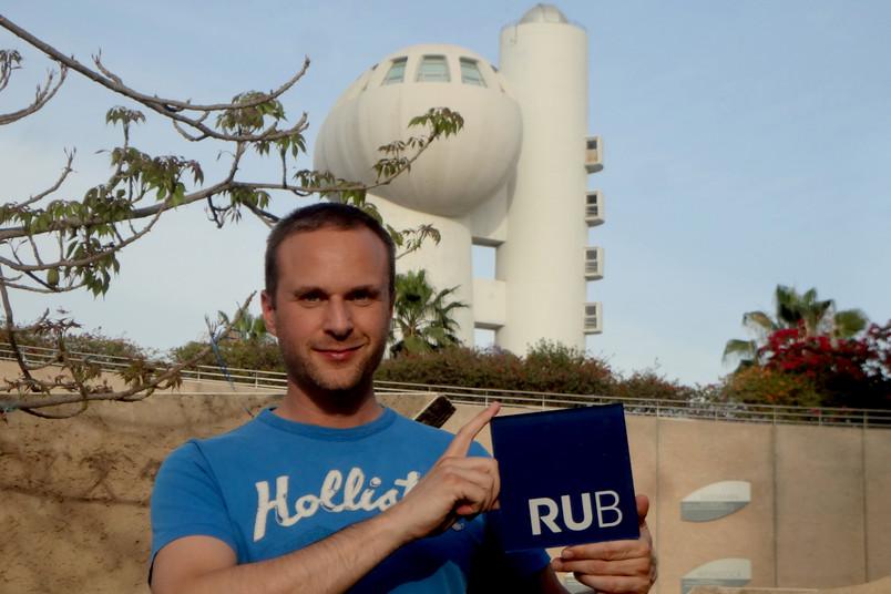 Benjamin Born präsentiert den RUB-Würfel am Koffler-Beschleuniger vor dem Weizmann Institut.