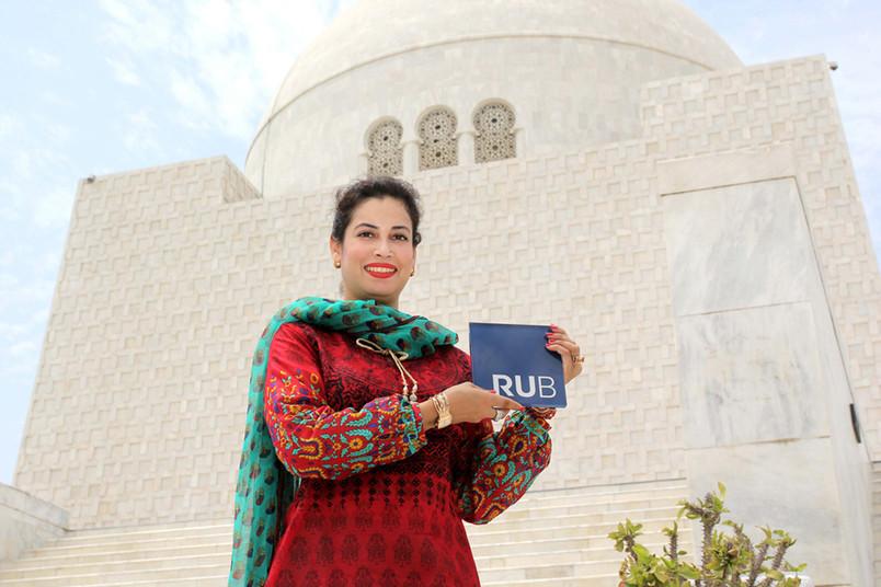 Der RUB-Würfel in Karachi: Sonia Siddiqui präsentiert ihn vor dem Jinnah Mausoleum.