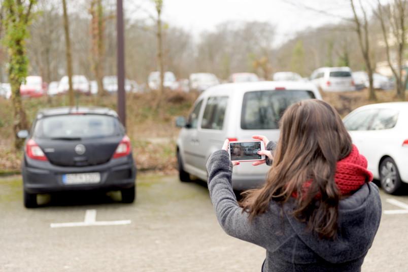Eine brünette Frau fotografiert mit ihrem Smartphone parkende Autos.
