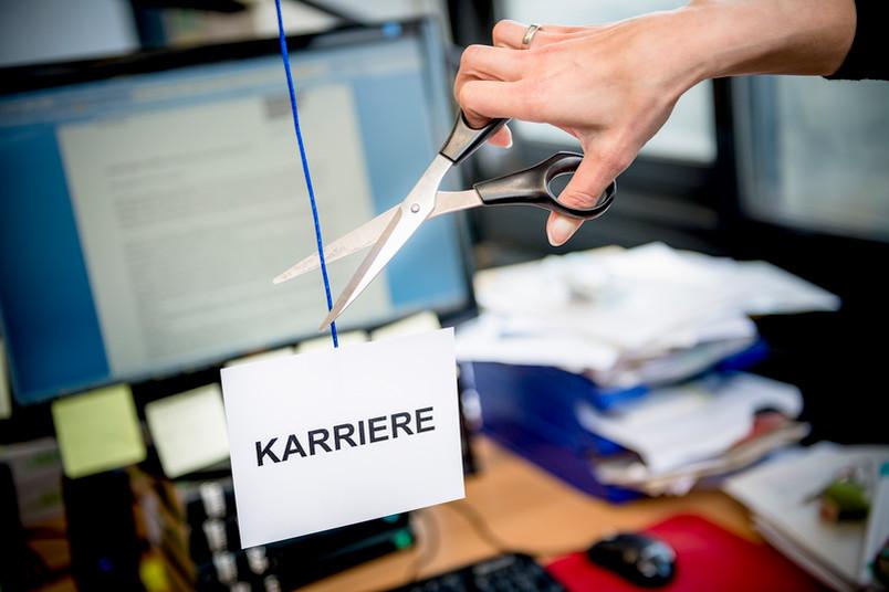 Mit einer Schere wird ein blaues Band zerschnitten. Am Ende des Bandes hängt ein Schild mit der Aufschrift Karriere.
