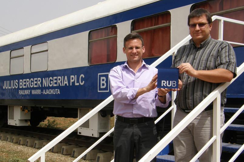 Jörg Wallesch (rechts) und sein Arbeitskollege Achim Becker stehen vor dem Museumszug von Julius-Berger-Nigeria. Sie haben schon zusammen an der RUB Bauingenieurwesen studiert.