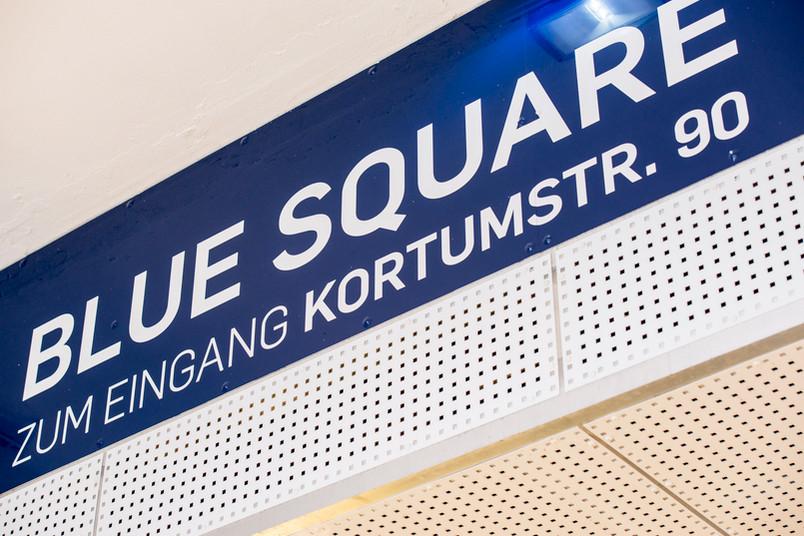 Schild am Gebäude des Blue Square.