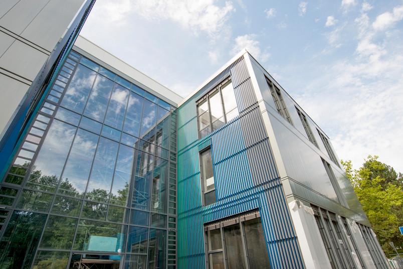 Moderne Glasfassaden und farbliche Akzente bestimmen den Haupteingang des Forschungsbaus.