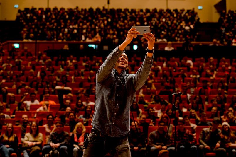 Moderator Efkan Yildirim macht ein Selfie mit den Erstsemestern im Publikum.