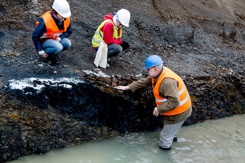 Ein Geologe steht in einer Baugrube und schaut sich ein Kohleflöz in der Gesteinswand an.