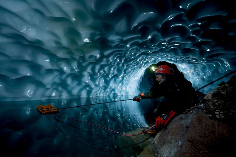 Andreas Pflitsch versenkt Sensoren für die Messung der Wassertemperatur in einer Eishöhle auf dem Gipfel des Mount Rainier.