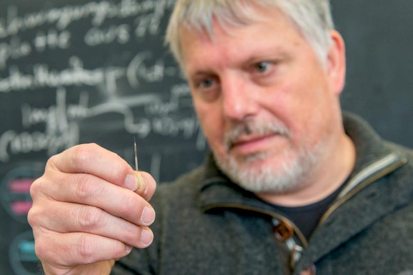 Forscher Wolfgang Schuhmann hält eine winzige Elektrode in der Hand, die die Konzentration von positiv geladenen Ionen messen kann.