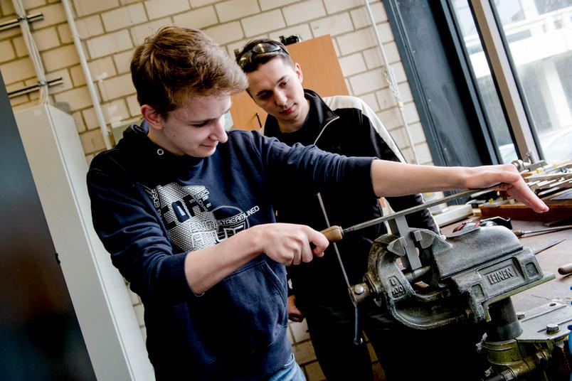 Thomas Konieczny (RUB-Azubi) zeigt Bastian Sack, wie man feilt.