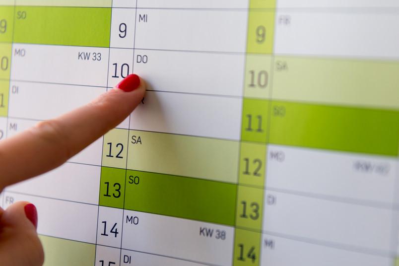 Eine Person zeigt auf einen Termin in einem Wandkalender ein.