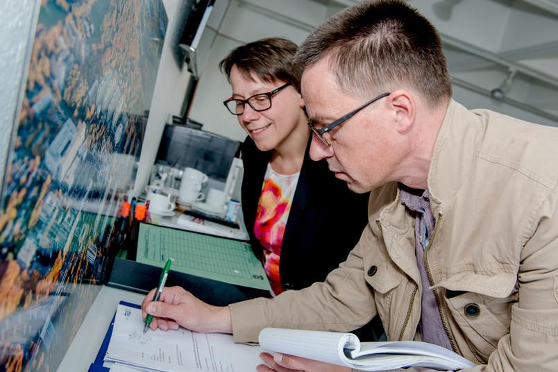 Rubens-Redakteur Arne Dessaul zeichnet symbolisch die Post ab. Kanzlerin Dr. Christina Reinhardt sieht ihm zu.
