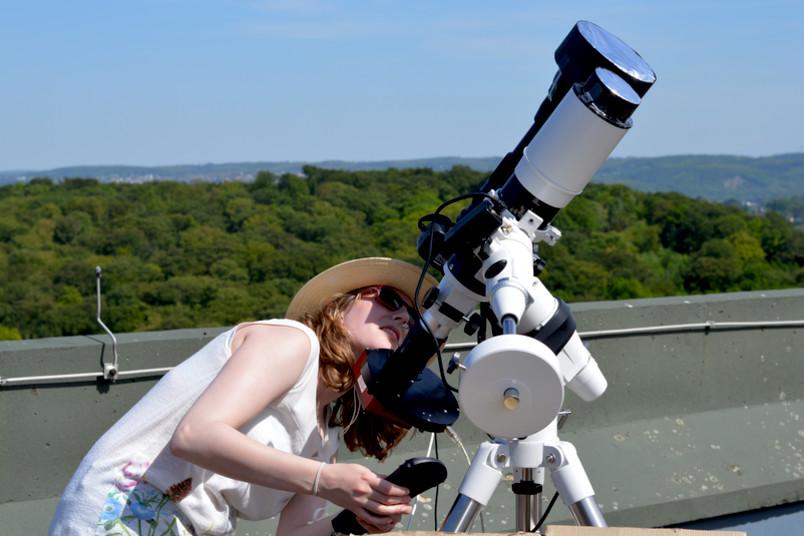 Eine wissenschaftliche Mitarbeiterin blickt durch ein Teleskop.