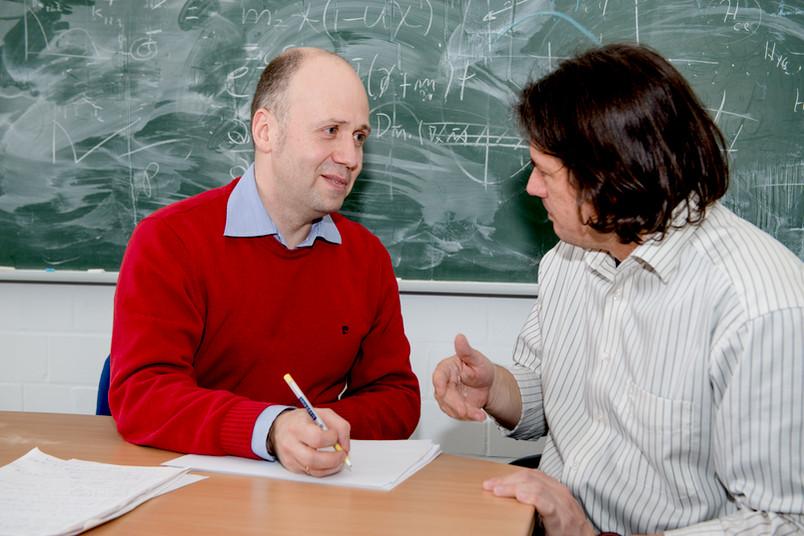 Zwei Wissenschaftler sitzen vor einer Tafel mit mathematischen Formeln und diskutieren.