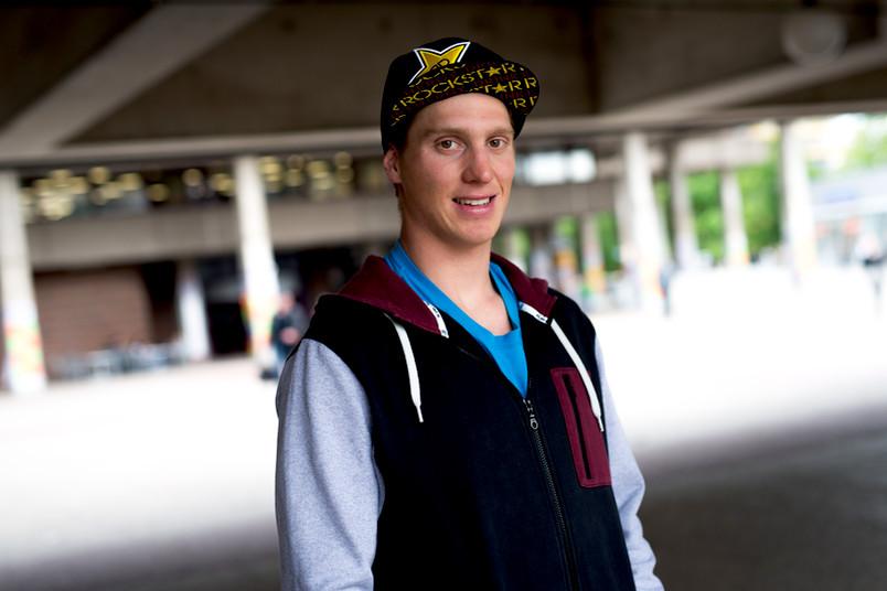 Junger Mann mit Baseballkappe steht vor einem Gebäude.