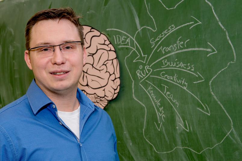 Mann mit Brille steht vor einer Tafel.