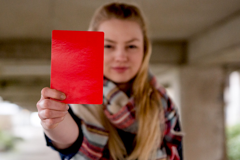 Eine junge Frau zeigt eine rote Karte