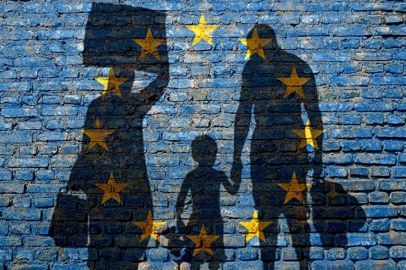 Flüchtlinge vor der Europaflagge.
