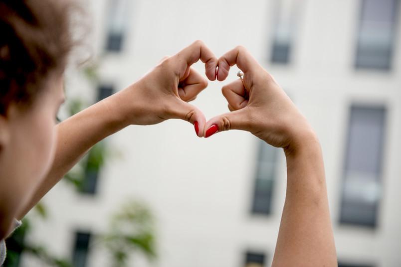 Eine Frau formt mit ihren Fingern ein Herz.