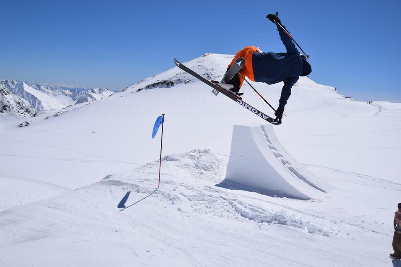 Skifahrer springt über einen Schneehügel und macht einen Trick in der Luft.