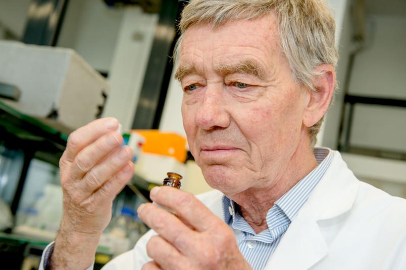 Ein Forscher riecht an einem kleinen Fläschchen.