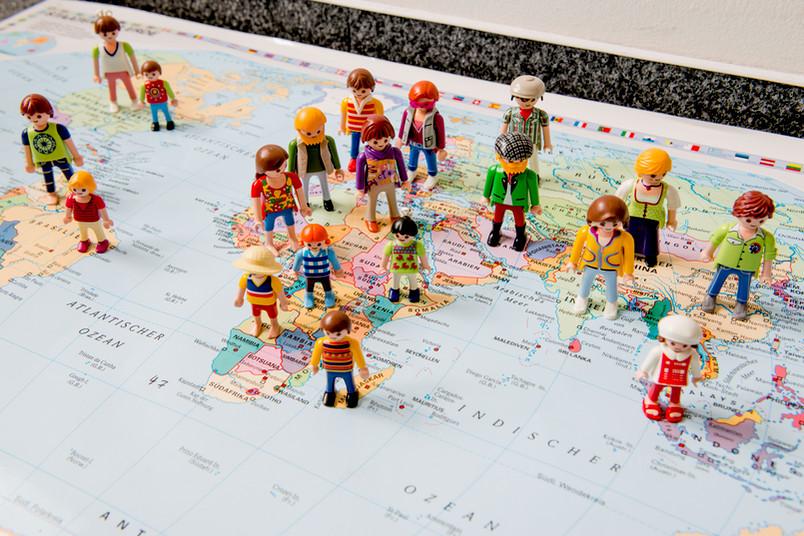 Playmobilfiguren auf einer Weltkarte