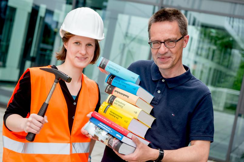 Eine junge Frau mit Helm, Warnweste und Hammer sowie ein Mann mit Bücherstapel posieren vor einem Gebäude.