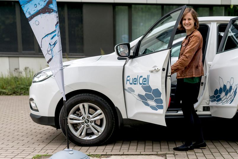 Junge Frau steigt in ein Brennstoffzellenauto ein.