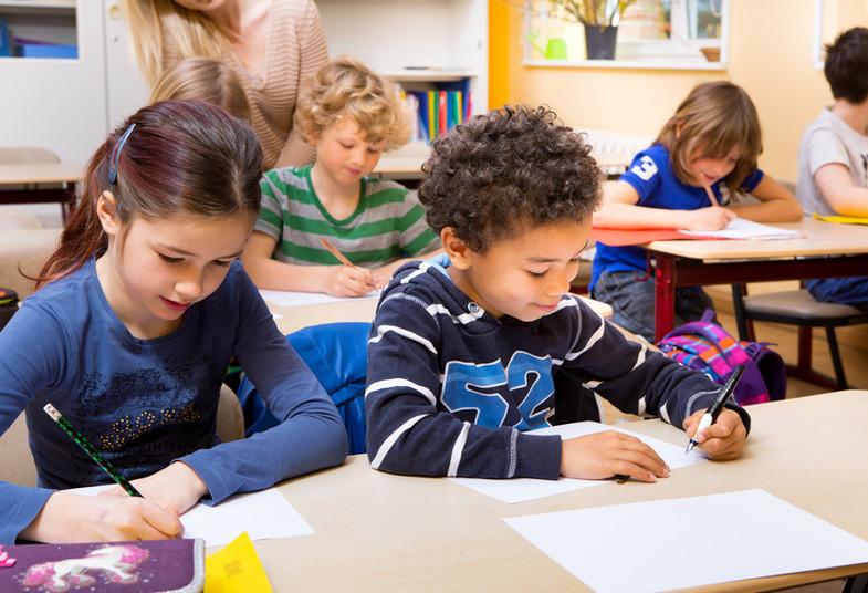 Kinder sitzen an einem Tisch und schreiben etwas in ihre Hefte.