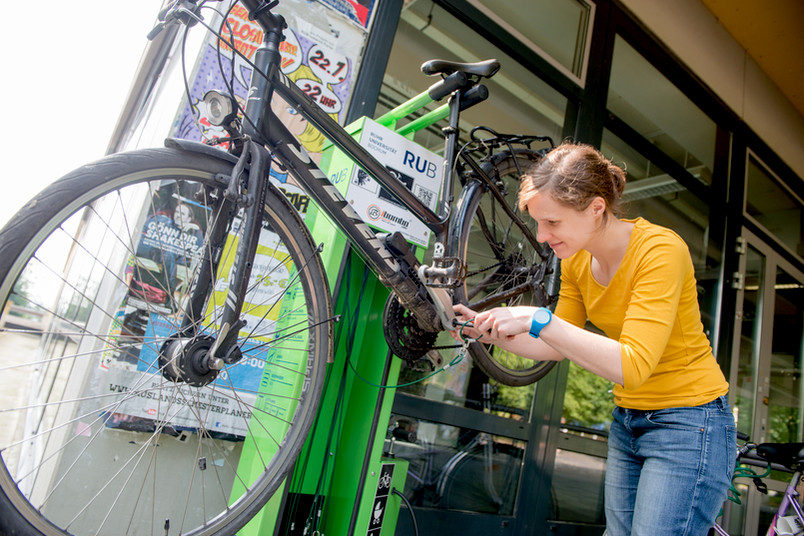 Junge Frau repariert ein Fahrrad.