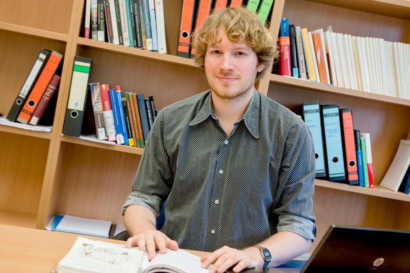 Porträt eines jungen Mannes am Schreibtisch