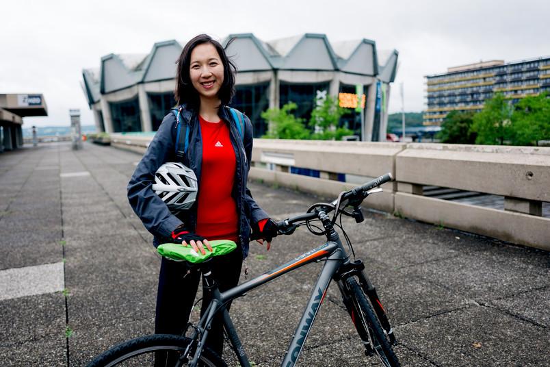 Junge Frau steht mit Fahrrad vor dem Audimax der RUB.