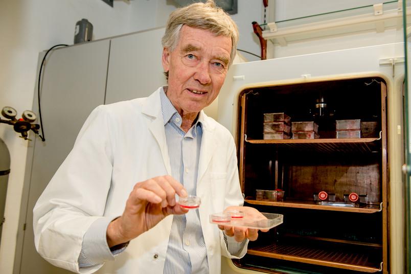 Ein Forscher vor einem Kühlschrank hält ein Schälchen in der Hand, in dem eine rote Flüssigkeit schwimmt