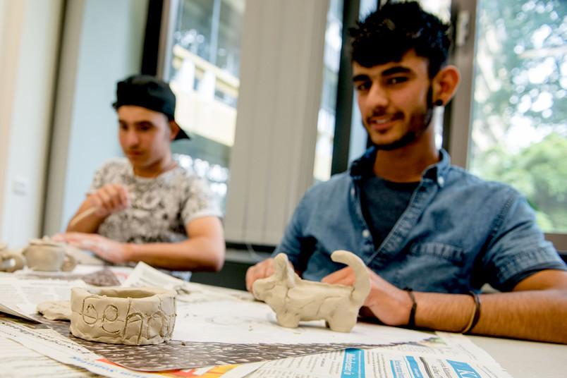 Schüler sitzt am Tisch und zeigt getöpferte Sachen.
