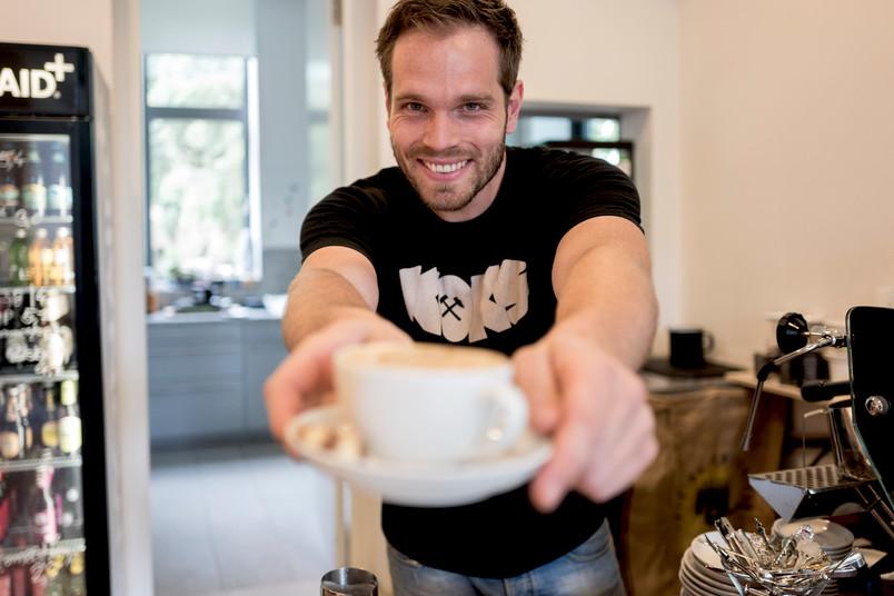 Mann hält Kaffeetasse im Kubus vor sich.