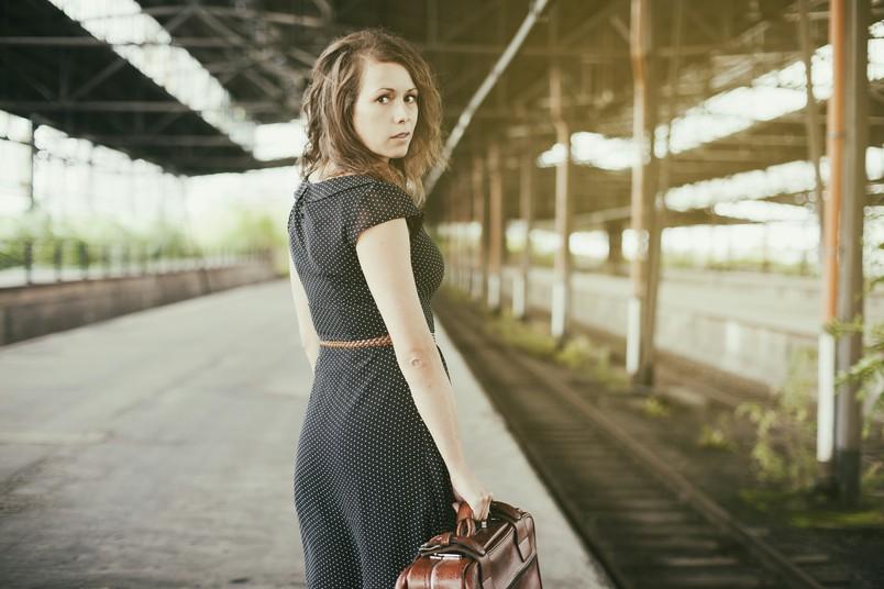 Katrin Hötzel steht mit einem Koffer in der Hand an einem Bahngleis.