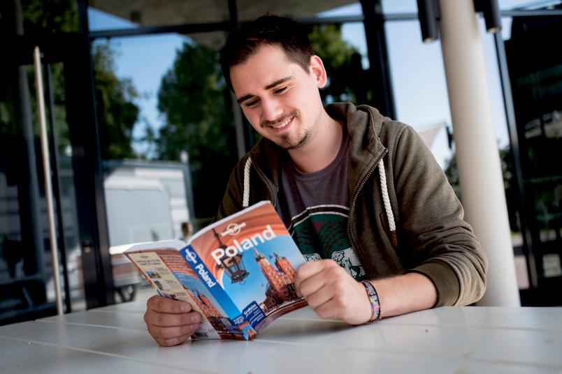 Student liest im Reiseführer über Polen.
