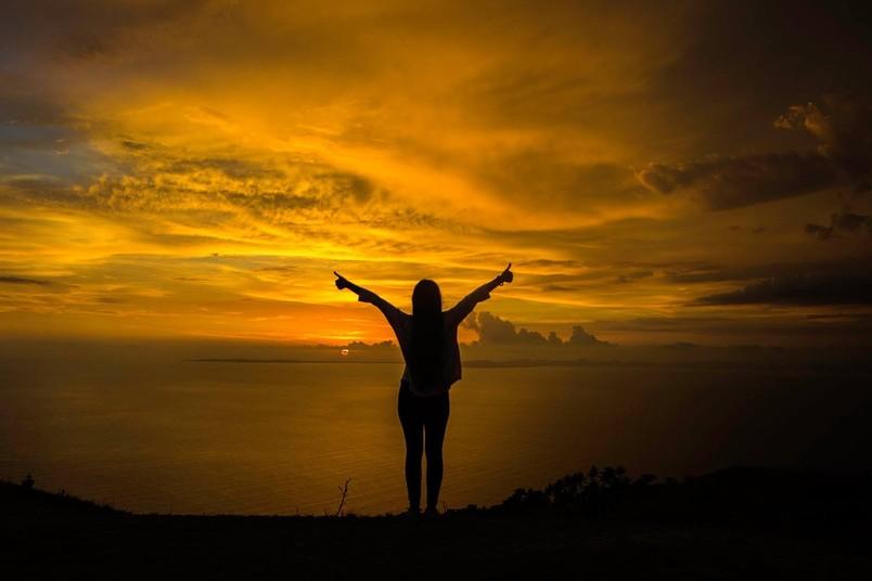 Personenumrisse vor einem Sonnenuntergang.